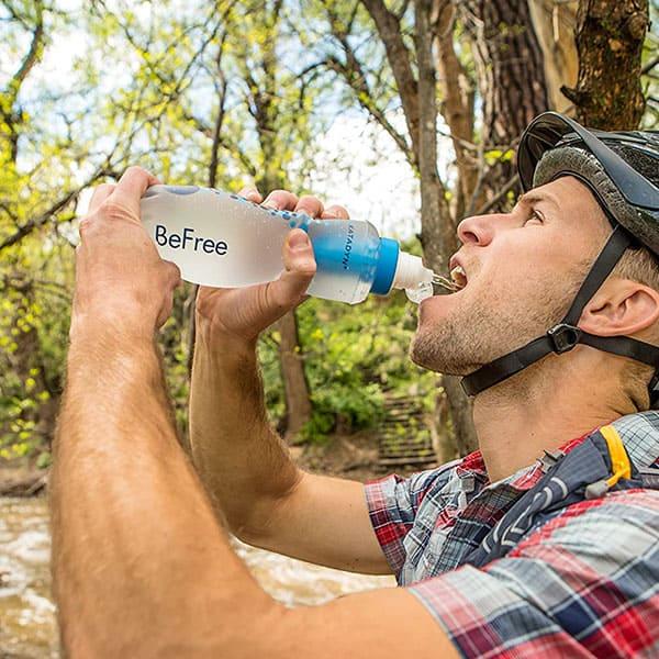 A guy drinking from a Katadyn BeFree water filter bottle