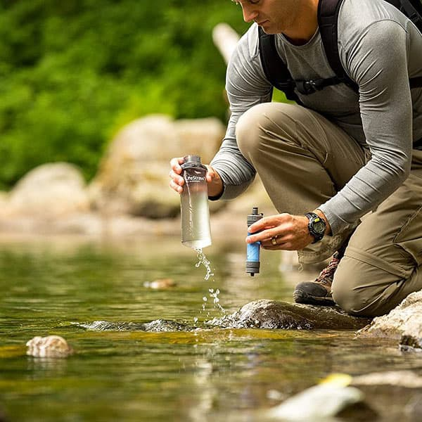 A backpacker using LifeStraw Flex to filter drinking water during hiking and camping