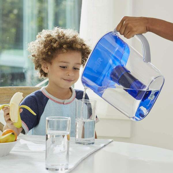 A Pur Water Filter Pitcher used to pour water on a glass for the smiling boy