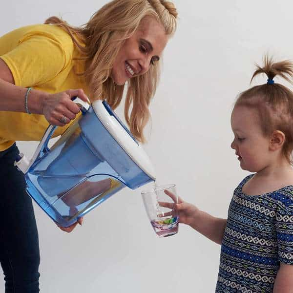A mom pouring out water to a childs' glass using the ZeroWater Filter Pitcher