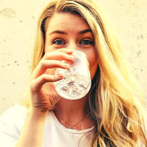 A woman drinking water on a glass