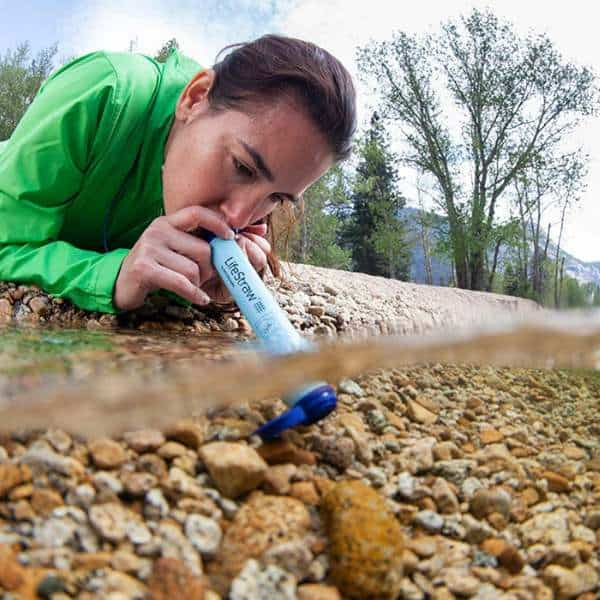 A woman sipping water from a mountain river using a LifeStraw filter