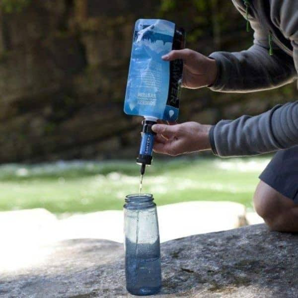 A man using the Sawyer Squeeze water filter to fill his water drinking bottle