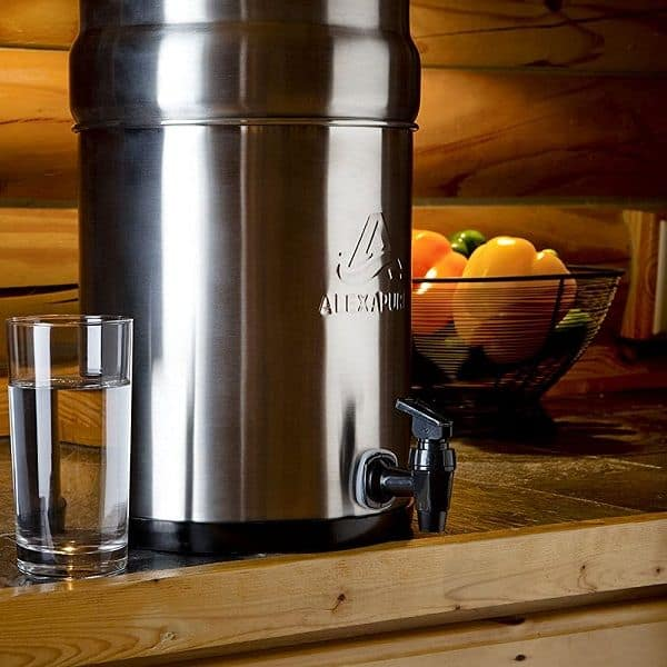 An Alexapure Pro Stainless Steel Water Filtration System beside a glass on the countertop