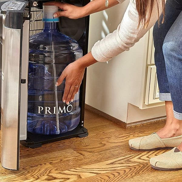 A woman setting up a bottom loading water dispenser with water