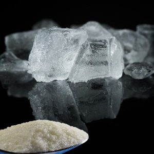 Water softener salt and ice cubes on a black surface